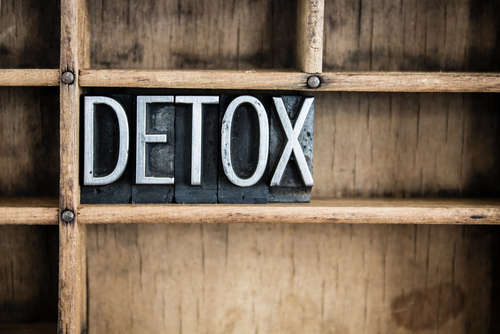 "The word ""DETOX"" written in vintage metal letterpress type in a wooden drawer with dividers."